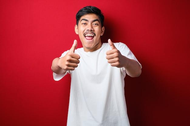 Jovem bonito vestindo camiseta branca sobre fundo vermelho, aprovando o gesto positivo com a mão, polegares para cima sorrindo e feliz pelo sucesso. gesto do vencedor.