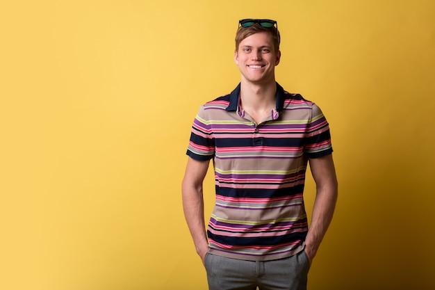 Jovem bonito vestindo camiseta casual em pé sobre a parede amarela, olhando com um sorriso no rosto, expressão natural. rindo confiante.