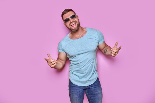 Jovem bonito vestindo camiseta casual em pé sobre fundo rosa isolado apontando com o dedo.