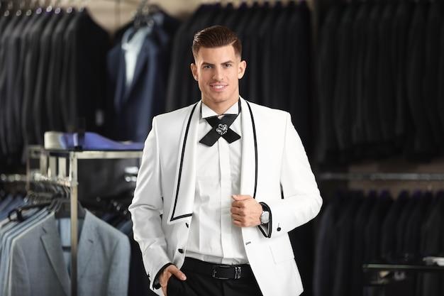 Jovem bonito vestindo um terno elegante na loja