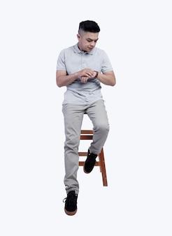 Jovem bonito vestindo uma camisa pólo cinza urze posava em uma cadeira