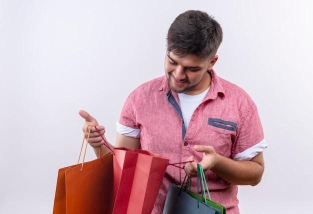 Jovem bonito vestindo uma camisa pólo rosa olhando para uma sacola de compras com curiosidade em pé sobre uma parede branca