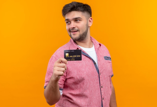 Jovem bonito vestindo uma camisa pólo rosa parecendo satisfeito, além de segurar um cartão de crédito em pé sobre uma parede laranja
