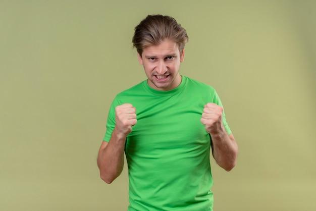 Jovem bonito vestindo uma camiseta verde cerrando os punhos com expressão agressiva em pé sobre a parede verde