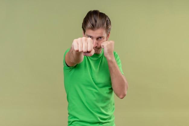 Jovem bonito vestindo uma camiseta verde posando como um boxeador com o punho cerrado em pé sobre uma parede verde