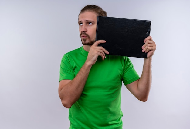 Jovem bonito vestindo uma camiseta verde segurando uma caixa de documentos, olhando para cima e pensando em pé sobre um fundo branco