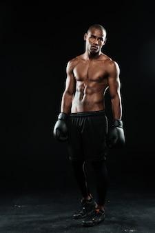 Jovem boxeador afro-americano em luvas, em pé