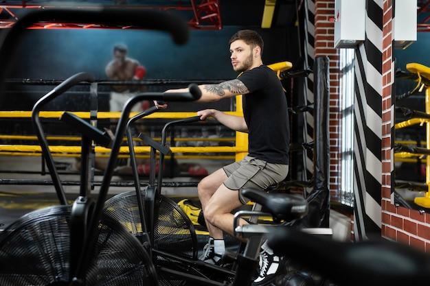 Jovem boxeador atlético treina em uma bicicleta ergométrica perto do ringue.