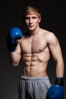 Jovem boxeador bonito em luvas azuis