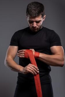 Jovem boxeador fazendo bandagens antes do treino