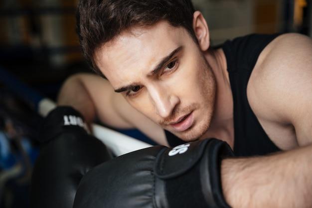 Jovem boxeador forte treinando em um ringue de boxe.