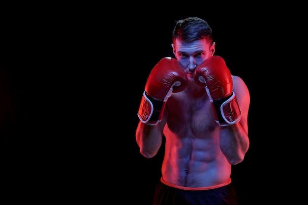 Jovem boxeador musculoso em luvas de boxe pronto para lutar contra seu rival na parede preta