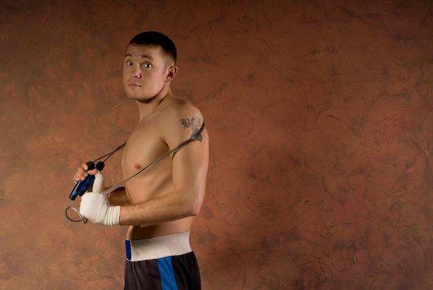 Jovem boxeador na academia com uma corda de pular