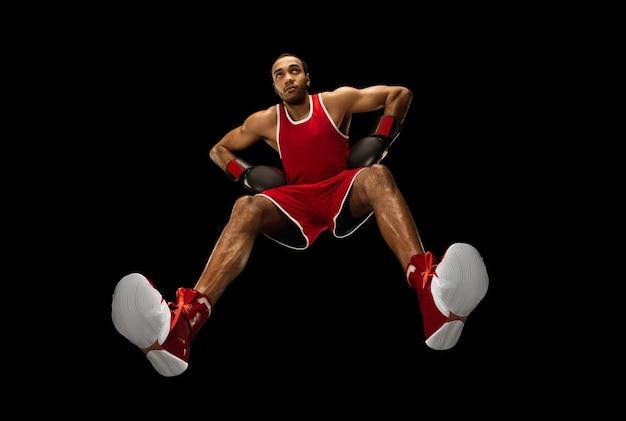 Jovem boxeador profissional afro-americano em ação, movimento isolado na parede preta, olhe de baixo. conceito de esporte, movimento, energia e estilo de vida dinâmico e saudável. treinando, praticando.