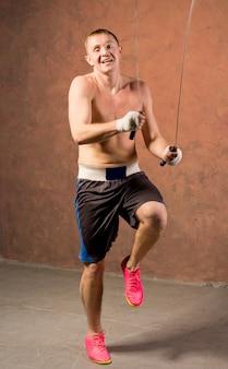 Jovem boxeador rindo enquanto treina com uma corda