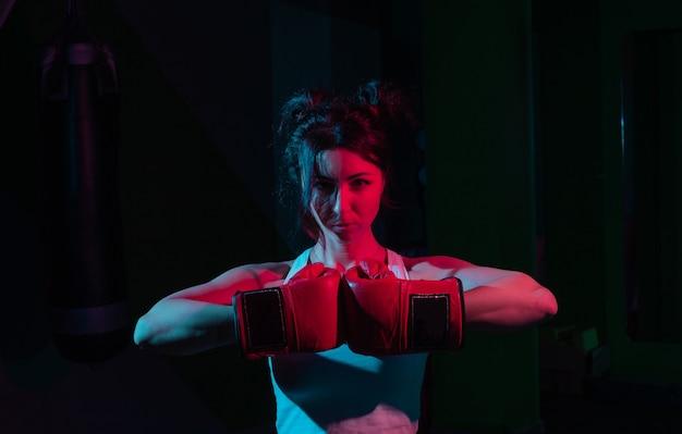 Jovem boxeadora com luvas de boxe em uma luz gradiente de néon vermelho azulada em uma parede escura