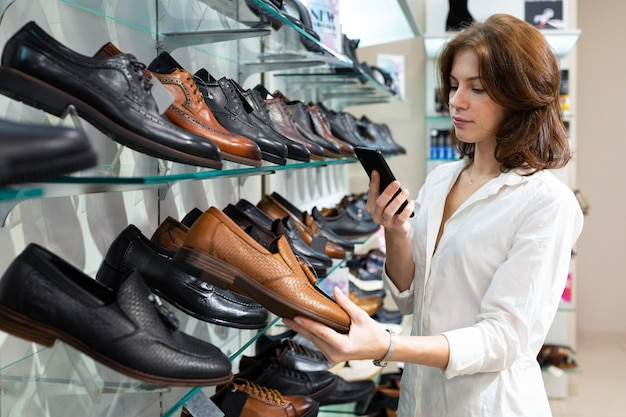 Jovem branca faz foto de sapatos de couro para homens.