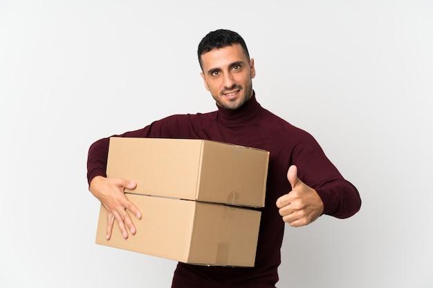 Jovem branco isolado, segurando uma caixa para movê-lo para outro site com o polegar para cima
