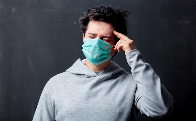 Jovem branco na máscara protetora com dor de cabeça