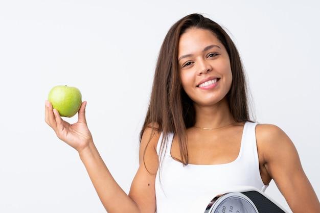 Jovem brasileira com uma balança e uma maçã