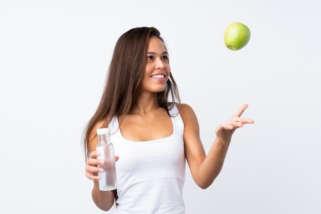 Jovem brasileira com uma maçã e uma garrafa de água sobre