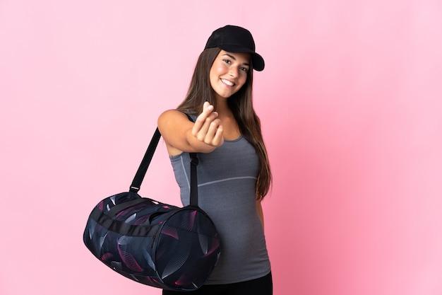 Jovem brasileira esportiva com bolsa esportiva isolada em rosa fazendo gesto de dinheiro