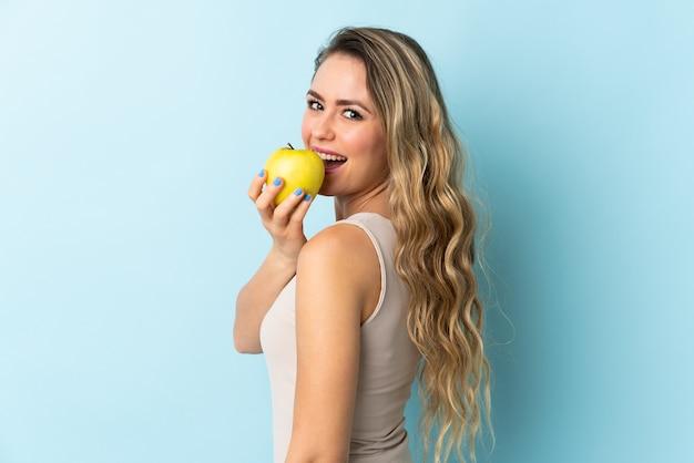 Jovem brasileira isolada comendo uma maçã