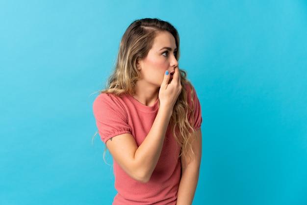 Jovem brasileira isolada em azul, fazendo o gesto de surpresa enquanto olha para o lado