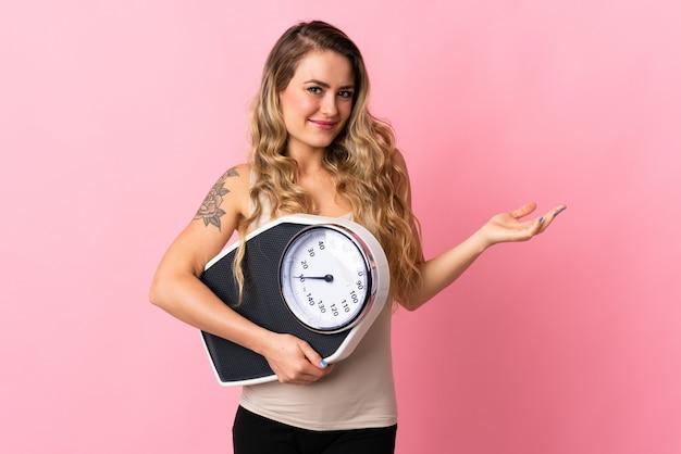 Jovem brasileira isolada em rosa com máquina de pesagem