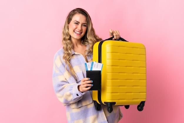 Jovem brasileira isolada em rosa em férias com mala e passaporte