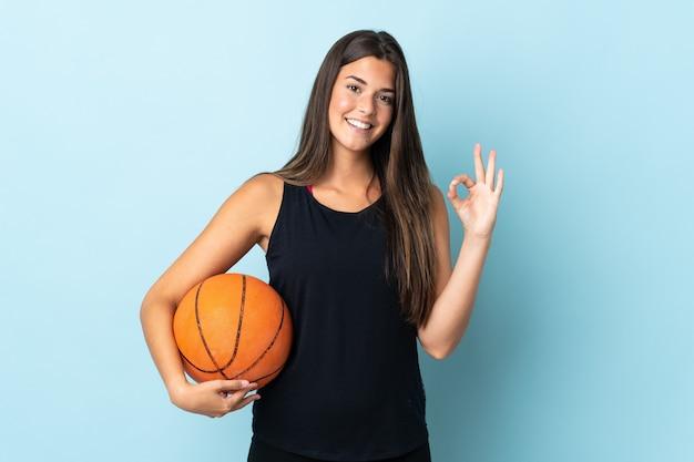 Jovem brasileira isolada em um fundo azul jogando basquete e fazendo sinal de ok