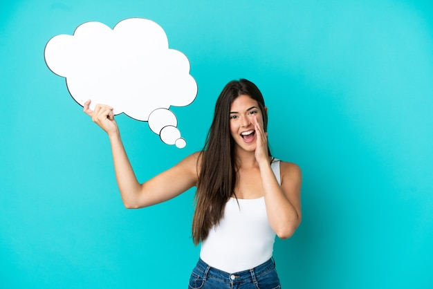 Jovem brasileira isolada em um fundo azul segurando um balão de pensamento e gritando