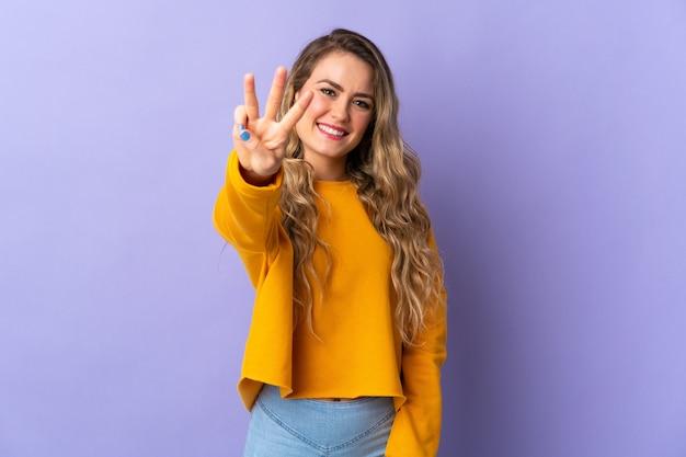 Jovem brasileira isolada em um fundo roxo feliz e contando três com os dedos