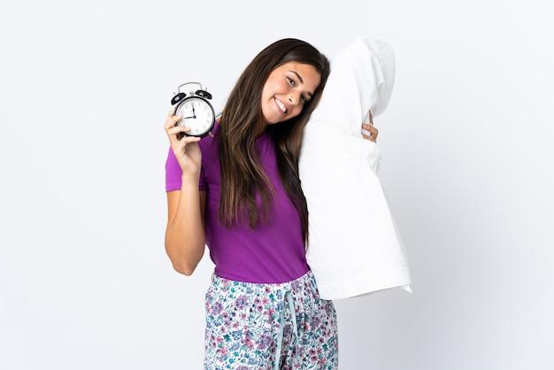 Jovem brasileira isolada no branco de pijama segurando o relógio e o travesseiro com uma expressão feliz