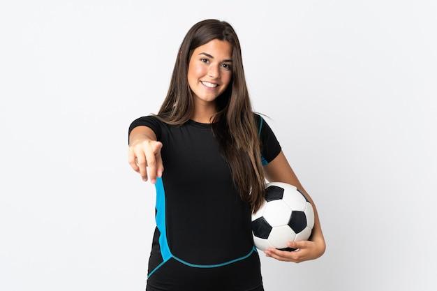 Jovem brasileira isolada no fundo branco com bola de futebol apontando para a frente