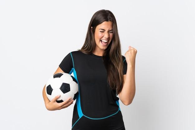 Jovem brasileira isolada no fundo branco com uma bola de futebol comemorando vitória