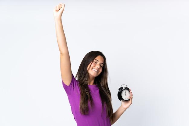 Jovem brasileira isolada no fundo branco de pijama e segurando o relógio fazendo gesto de vitória