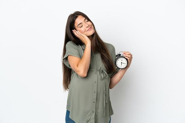 Jovem brasileira isolada no fundo branco grávida e segurando o relógio fazendo gestos para dormir