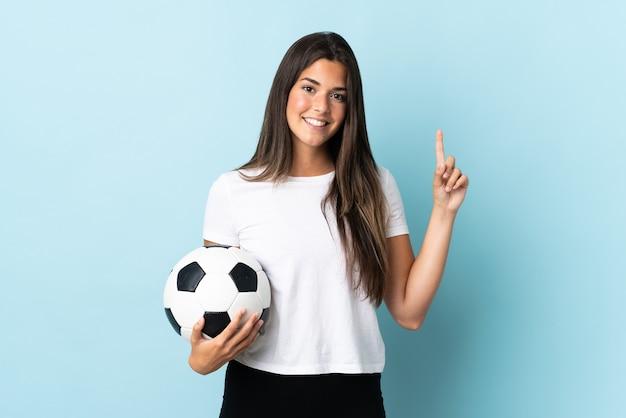 Jovem brasileira jogadora de futebol isolada em um fundo azul apontando uma ótima ideia