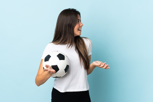 Jovem brasileira jogadora de futebol isolada em um fundo azul com expressão de surpresa ao olhar de lado