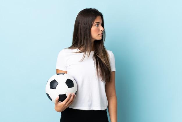 Jovem brasileira jogadora de futebol isolada em um fundo azul olhando para o lado