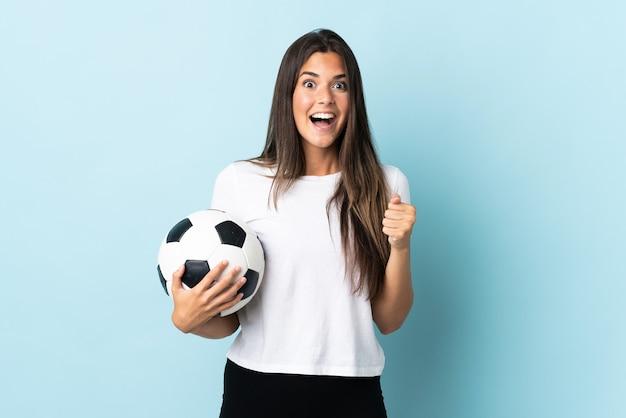 Jovem brasileira jogadora de futebol isolada no azul comemorando vitória na posição de vencedora