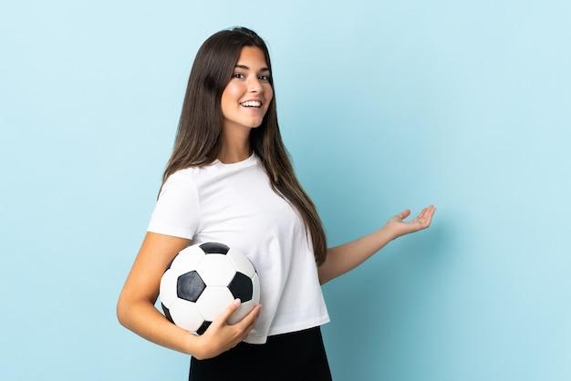 Jovem brasileira jogadora de futebol isolada no azul estendendo as mãos para o lado para convidar para vir