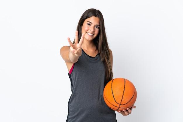 Jovem brasileira jogando basquete isolado em um fundo branco feliz e contando três com os dedos