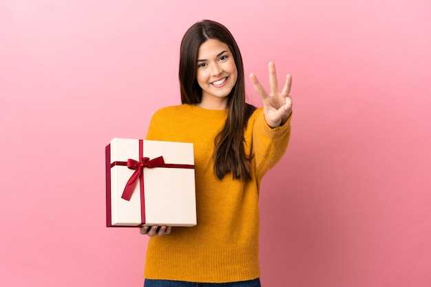 Jovem brasileira segurando um presente sobre um fundo rosa isolado feliz e contando três com os dedos