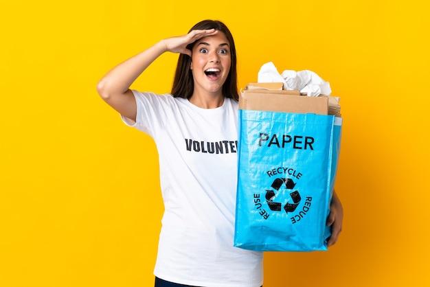 Jovem brasileira segurando uma sacola cheia de papel para reciclar isolada em um fundo amarelo com expressão de surpresa