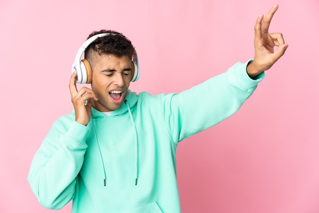 Jovem brasileiro em uma parede isolada ouvindo música com um celular e cantando
