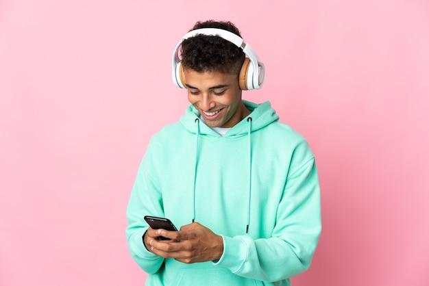 Jovem brasileiro em uma parede isolada ouvindo música e olhando para o celular