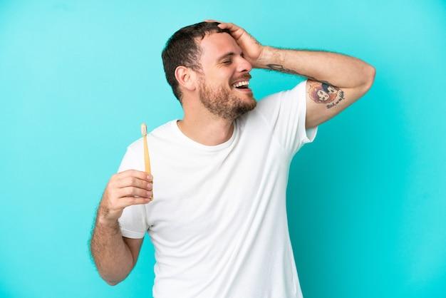 Jovem brasileiro escovando dentes isolado em fundo azul sorrindo muito