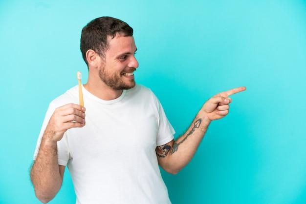 Jovem brasileiro escovando dentes isolados em fundo azul apontando o dedo para o lado e apresentando um produto